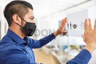 Geschäftsmann mit Maske befestigt Hygienekonzept im Büro