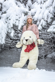 Woman out in the snow with a large soft toy