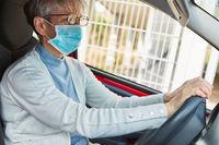 Seniorin beim Auto fahren mit Mundschutz
