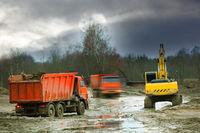 Excavator loads excess soil into dump trucks