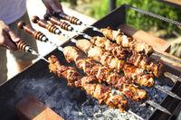 Man cooking marinated shashlik, lamb meat grilling on metal skewer
