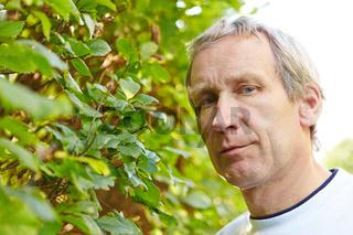 Alter Mann neben Hecke im Garten