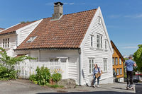 People walking through traditional streets of Stavanger in Norway, which is one of most famous cruise travel destinations in Europe