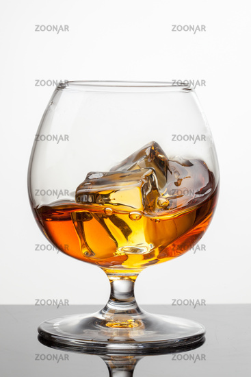 Splash of whiskey with ice in glass isolated on white background. Raw photo