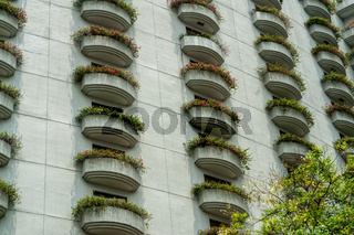 Close-up photo of balconies covered with flowers. Abstract on the subject of modern architecture,landscaping buildings, building exterior, construction industry or technology. Details of balcony.
