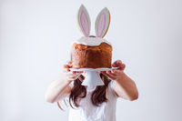 Portrait of gir holding Easter bread on stand in front of her