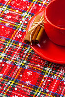 Photo of red cup of coffee, cinnamon and placemats.