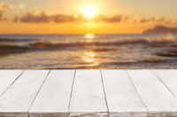 Empty white wooden boards or countertop against seascape with sunset on background. Template, mockup for display or montage of products. Close up
