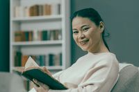 Cute Young Woman Smiling Holding Old Book In Her Hands