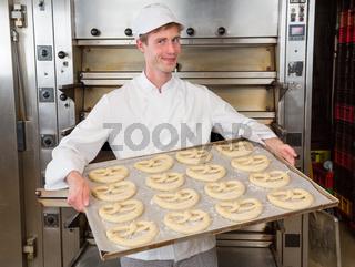 Baker with baking plate full of pretzels