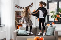 girls in halloween costumes jumping on sofa