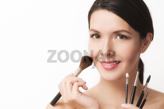 Beautiful woman with cosmetic brushes