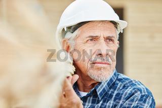 Senior Handwerker trägt Holz auf Baustelle