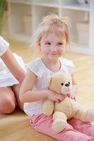 Mädchen spielt mit Teddybar auf Schoß