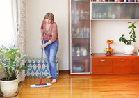 Adult lady cleaning floor at home