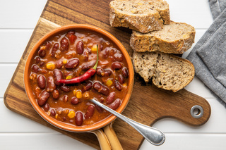 Chili con carne. Mexican food with beans in pot and bread