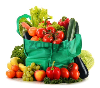 Green shopping bag with variety of fresh organic vegetables isolated on white
