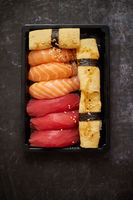 Nigiri sushi set in plastic container ready for takeout delivery. Closeup of take away lunch box