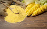 Ripe young sweet corn cob spoon and cornmeal on background
