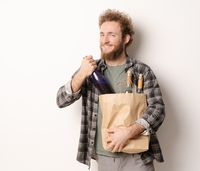 Back from shopping holding a paper bag with bottles of wine smiling young man. Handsome young man with curly hair in olive t-shirt looking at camera isolated on white background