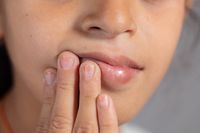 Extreme close up of child touch's her mouth - concept showing to prevent and Avoid touching your Mouth. Protect from COVID-19 or coronavirus spreading or outbreak - Don t Touch Your mouth.