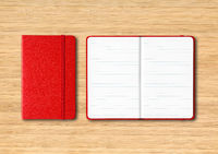 Red closed and open lined notebooks on wooden background