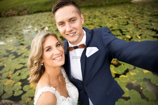 Wedding selfie. Bride and groom hugging tenderly posing during photo shooting in park.