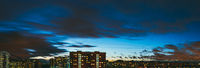 Night long panorama of the roofs of the buildings and lit windows