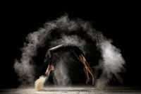 Male gymnast jumping in dust cloud profile view