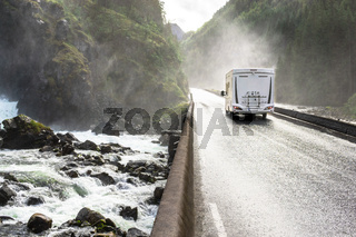Motorhome Camper Van driving fast on wet canyon valley road and bridge across waterfall river. Norway.