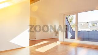 Sonniger leerer Raum mit Balkon im Dachgeschoss