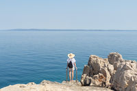 Woman traveler wearing straw summer hat and backpack, standing at edge of the rocky cliff looking at big blue sea and islands in on the horizon