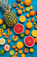 Flat lay layout of summer and citrus fruits on blue background.  Healthy eating concept.
