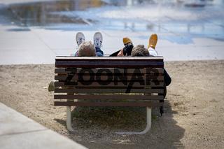 liegendes entspanntes Paar auf einer Parkbank