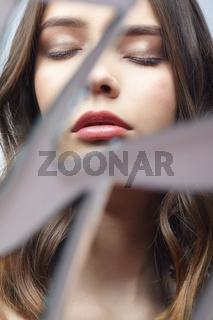 Young woman with eyes closed in mirror. Portrait of beautiful female in the mirror shards