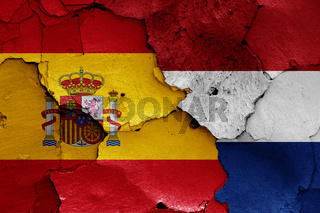 flags of Spain and Netherlands painted on cracked wall