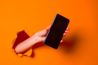 A woman holds a phone through ragged orange paper background, close-up.