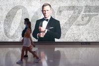 Singapur, Republik Singapur, Personen mit Mundschutz vor einer Werbung fuer James Bond Film
