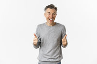 Image of amazed and happy middle-aged man, showing thumbs-up and smiling, standing over white background