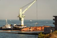 Industrial ship crane lifts old sunken tanker Delfi from Black Sea in Odessa, Ukraine 26 August 2020. Ship crashed near shore sea. Cargo tanker. Ecological disaster oil spill products. Tanker Delphi