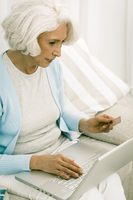 Gray haired woman use laptop for online shopping or banking