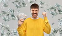 happy young man with money celebrating success