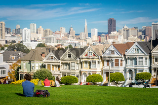 View on the Painted Ladies Victorian houses of San Francisco with cityscape and skyline in the background on a blue sky. People sitting front