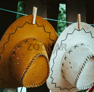 Two decorative leather hats hanging on a line