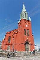 People relaxing in front of St. Petri Church or St. Petri Kirke, which is a parish church in Stavanger, Norway