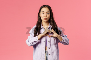 Portrait of romantic cute korean girl show heart gesture and fold lips, giving kiss, express sympathy, passion and romance, standing pink background in lovely stylish outfit