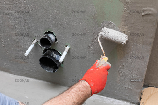A close-up view of an experienced construction worker applying damp insulation using a paint roller on a wall.