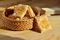 Sweet sugar cookies with jam in a wicker basket on a wooden background
