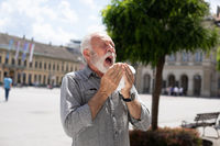 Old man man coughs and sneezes into a handkerchief on street, allergies and illness conceptz