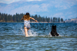 Dog and woman playing in a mountain lake